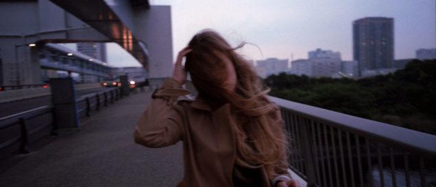 Девушка с растрёпанными волосами идет по городу в непогоду