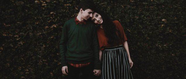 Влюбленные держатся за руки на фоне листвы